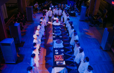performance photo of dining hall employees standing around table full of prepared food