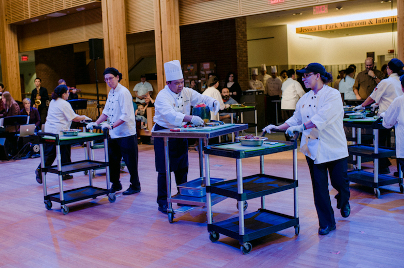 performance photo of dining hall workers pushing portable prep tables