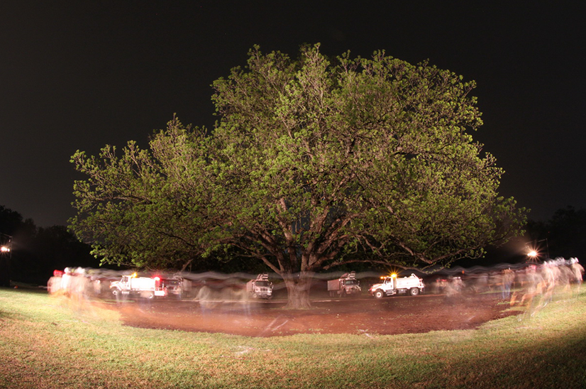 performance photo of people circling tree