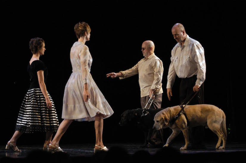 performance photo of sextet, two female dancers walking toward two men with their guide dogs